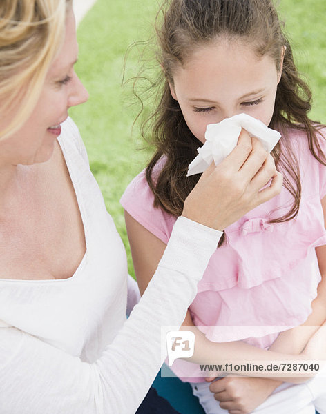 Mother helping daughter (8-9 years) to blow her nose