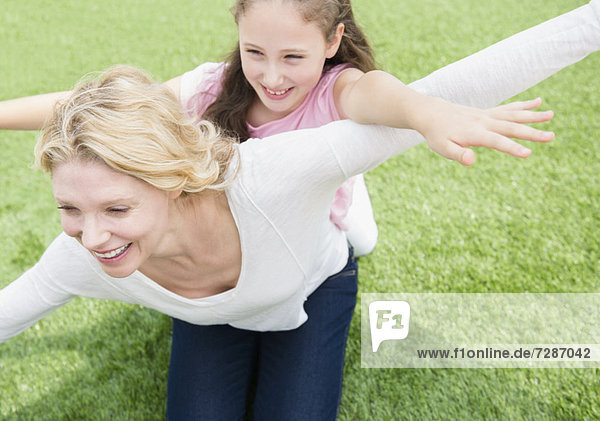 Mother and daughter (8-9 years) playing on meadow