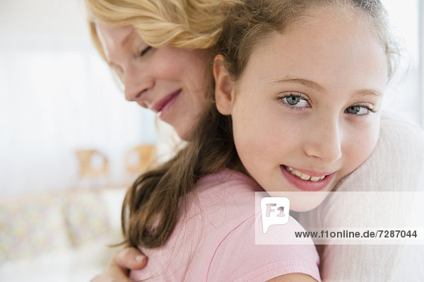 Mother and daughter (8-9 years) embracing