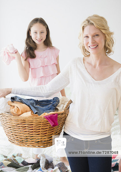 Mother and daughter (8-9) with laundry basket