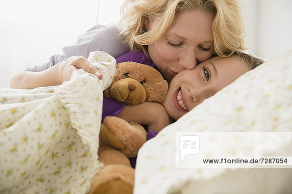 Mother and daughter (8-9) embracing in bed
