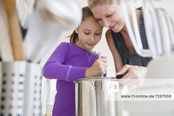 Mother and daughter (8-9) cooking together