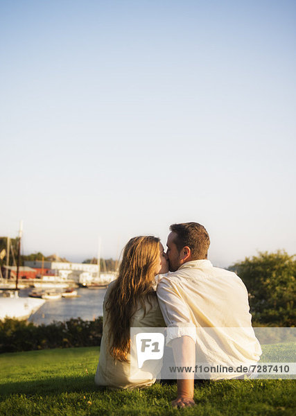 Couple kissing  harbor in background