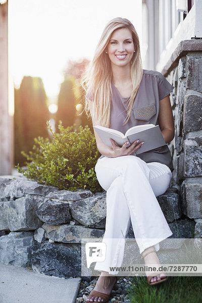 Außenaufnahme  sitzend  Portrait  Frau  Buch  halten  Taschenbuch  freie Natur