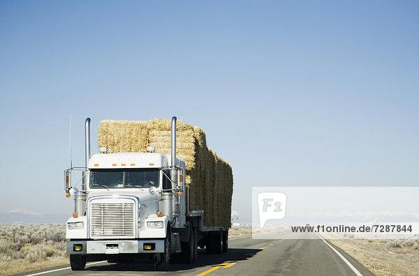 Truck hauling hay on rural road