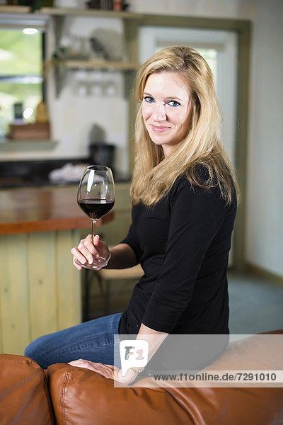 USA  Texas  Blonde Frau sitzt auf dem Sofa und hält ein Glas Rotwein.