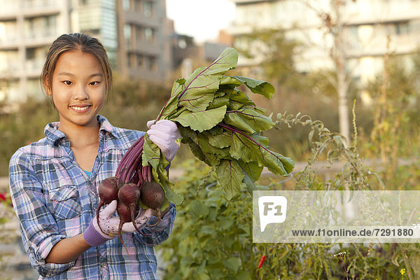Japanese girl holding bunch of beets