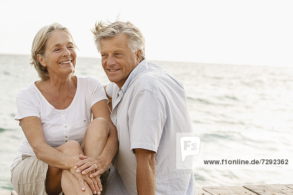 Spain  Senior couple sitting at the sea  smiling