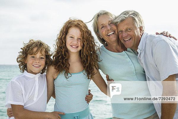 Spain  Grandparents with grandchildren at the sea  smiling  portrait