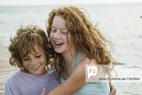 Spain  Girl and boy at the sea  smiling