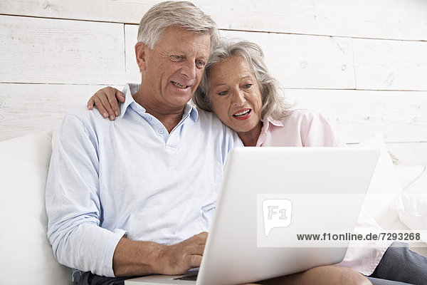 Spain  Senior couple checking emails on laptop  smiling