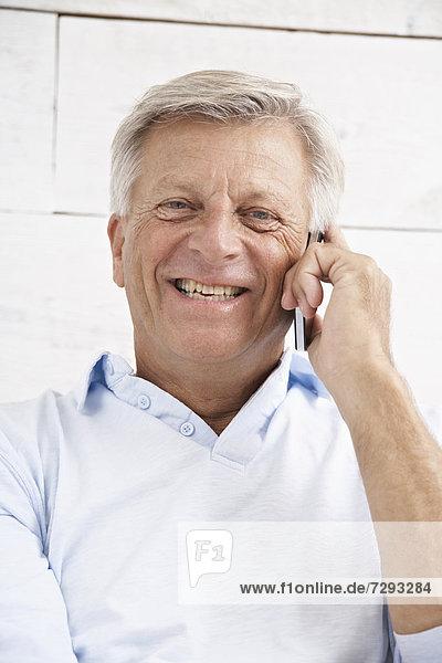 Spain  Senior man talking on mobile  smiling  portrait