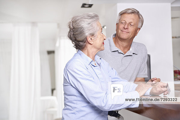Spain  Senior couple with credit card waiting at reception