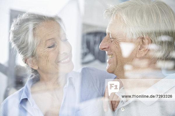 Spain  Senior couple behind window  smiling