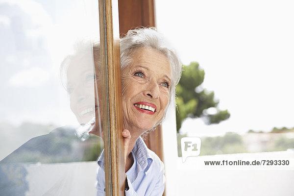 Spain  Senior woman looking through window  smiling