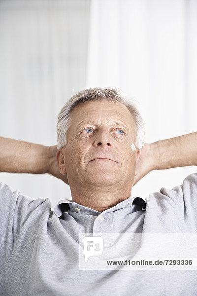 Spanien  Mallorca  Senior Mann sitzend mit den Händen hinter dem Kopf