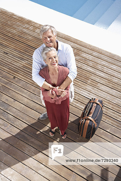 Spain  Senior couple standing with suitcase at swimming pool  smiling  portrait