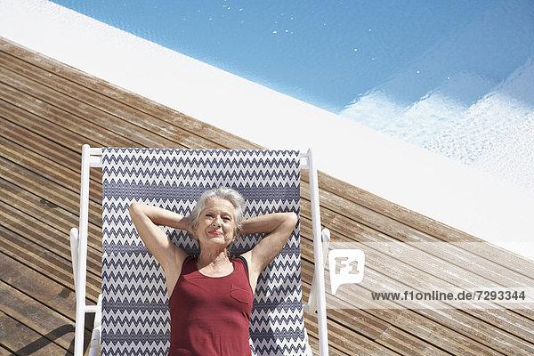 Spain  Senior woman relaxing on deck chair at beach