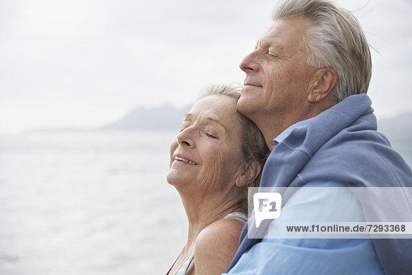 Spain  Senior couple on beach at Atlantic  smiling