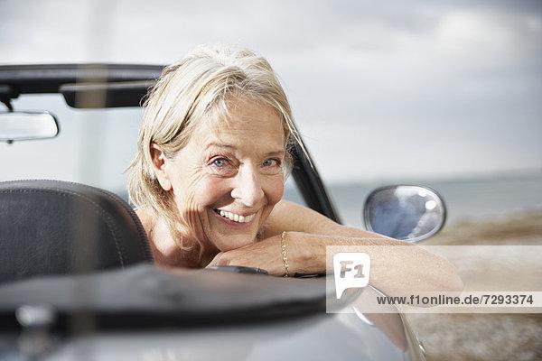 Spain  Senior woman in convertible car  smiling  portrait