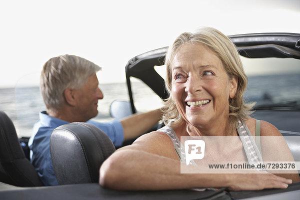 Spain  Senior couple in convertible car  smiling