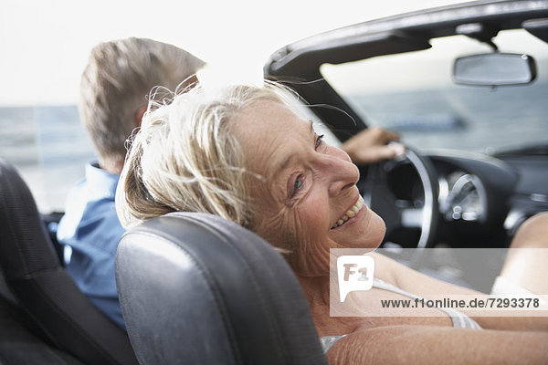 Spain  Senior couple in convertible car  smiling