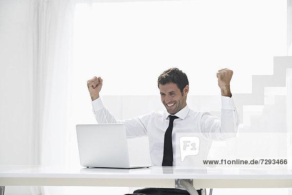 Spanien  Geschäftsmann aufgeregt bei der Suche nach Laptop  lächelnd