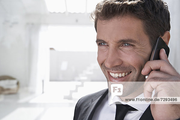Spain  Businessman talking on mobile phone  smiling