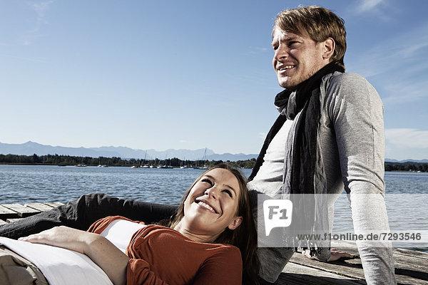 Germany  Bavaria  Couple sitting on jetty at Lake Starnberg