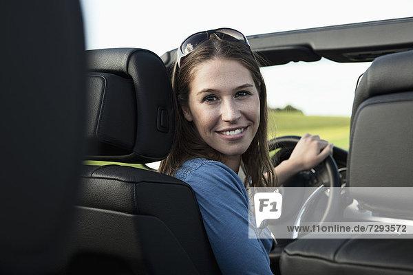 Junge Frau im Auto  lächelnd