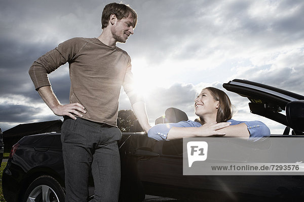 Germany  Bavaria  Couple standing by car  smiling