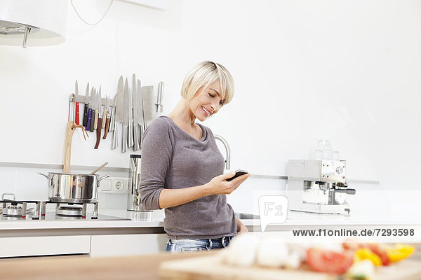 Woman using mobile in kitchen