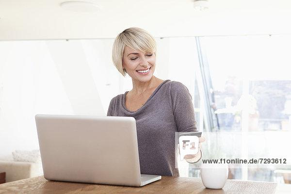 Frau einkaufen mit Kreditkarte auf dem Laptop