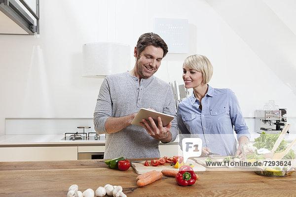 Deutschland  Bayern  München  Reife Paare beim Zubereiten von Speisen mit Blick auf digitale Tabletten