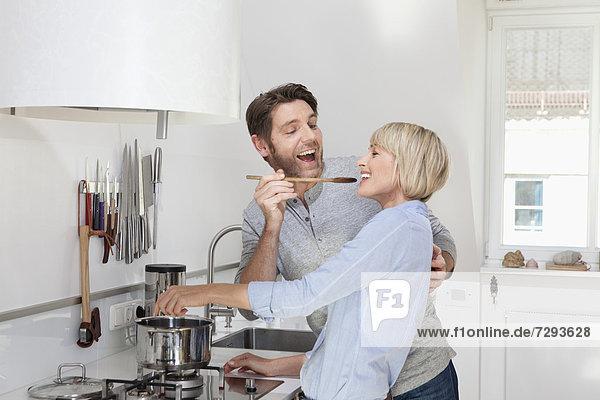 Reife Frau beim Kochen während der Fütterung des Mannes