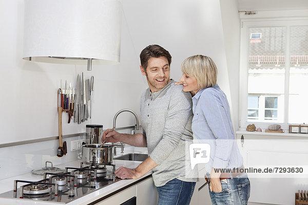 Deutschland  Bayern  München  Reife Paare bei der Zubereitung von Speisen in der Küche