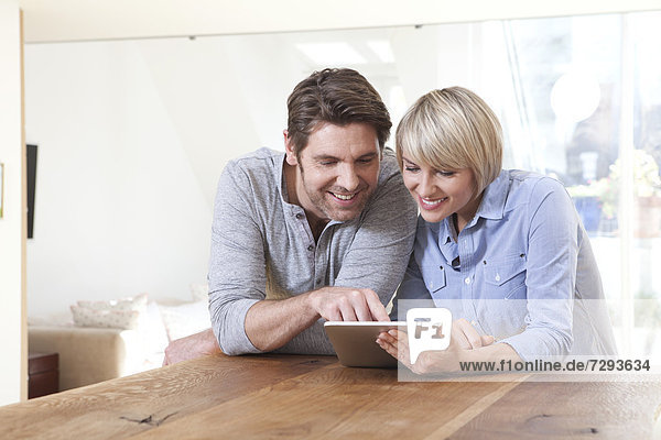 Germany  Bavaria  Munich  Mature couple using digital tablet  smiling