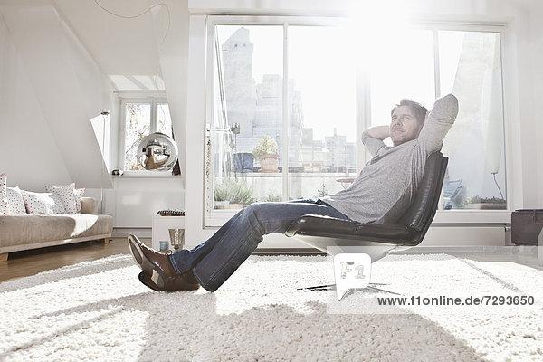 Mann auf Sessel sitzend