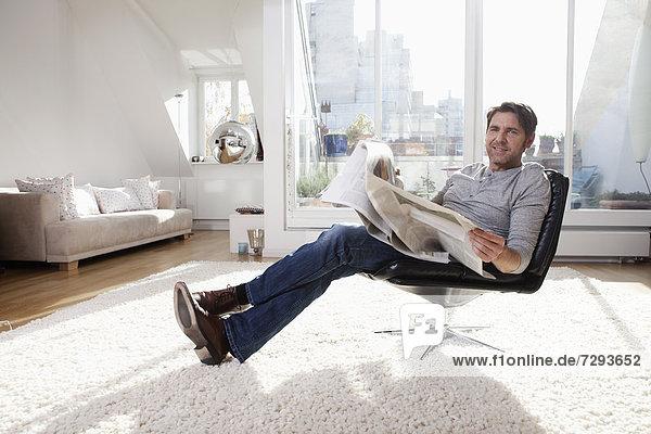 Mann liest Zeitung im Wohnzimmer