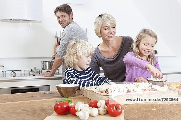Germany  Bavaria  Munich  Family preparing pizza in kitchen