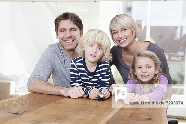 Germany  Bavaria  Munich  Portrait of family sitting at table  smiling
