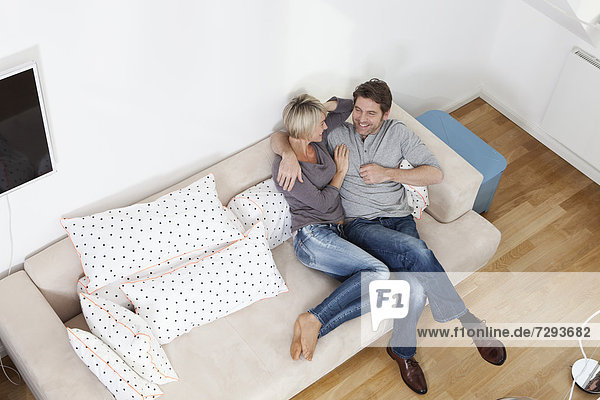 Germany  Bavaria  Munich  Mature couple relaxing on sofa  smiling