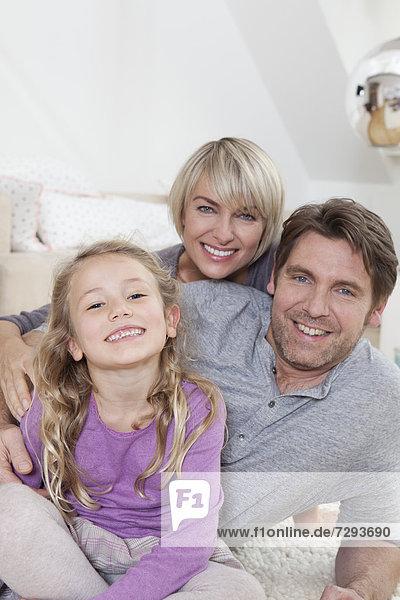 Germany  Bavaria  Munich  Family lying on floor  smiling  portrait