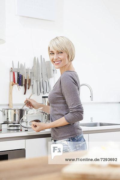 Frau bei der Zubereitung von Speisen in der Küche