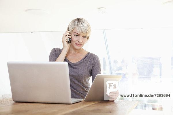 Frau arbeitet mit digitalem Tablett und spricht am Telefon