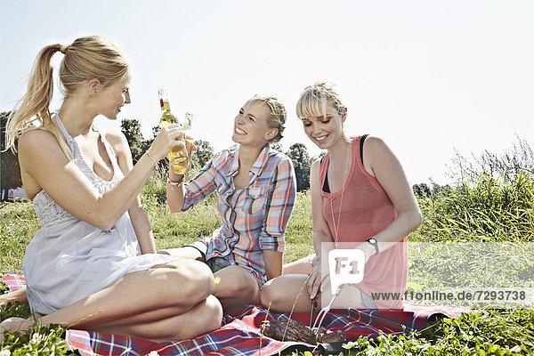 Junge Frauen trinken Bier beim Picknick