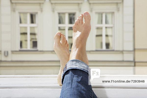 Junge Frau Füße auf offenem Fenster