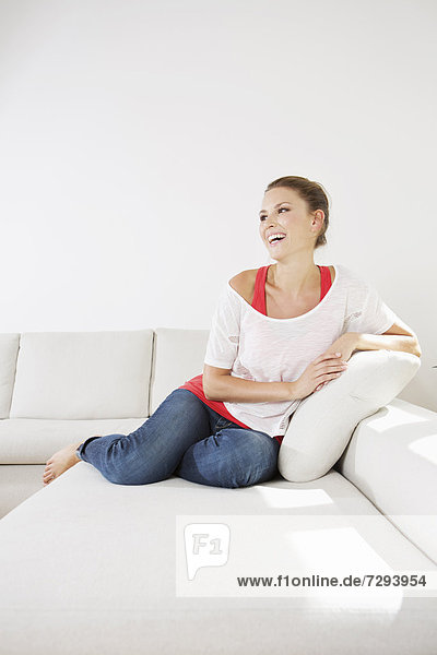 Young woman sitting on couch  smiling