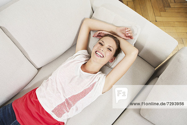 Young woman lying on couch  smiling
