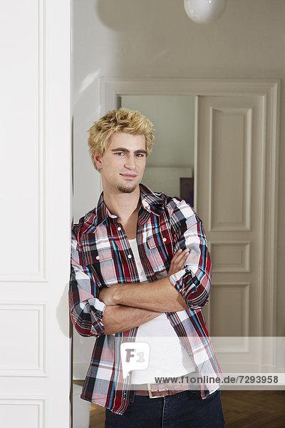 Young man standing beside door  smiling